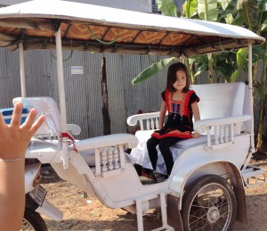 T in a thai dress, and riding a Cambodian tuk-tuk.